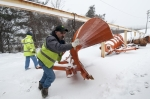 A heavy equipment operator moves an oversized plow to connect to the snow trucks during a storm in January.